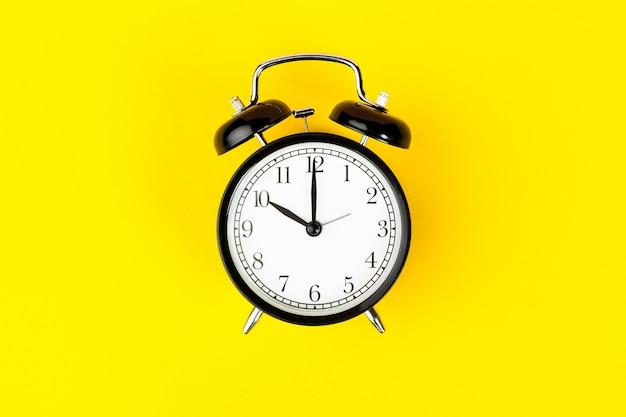 Alarm clock on bright yellow close up Premium Photo