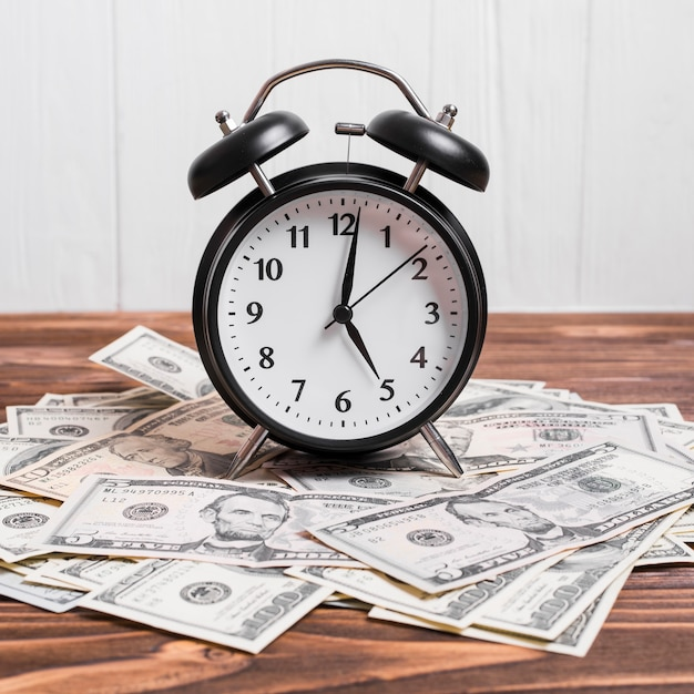 An alarm clock on currency notes over wooden table Free Photo