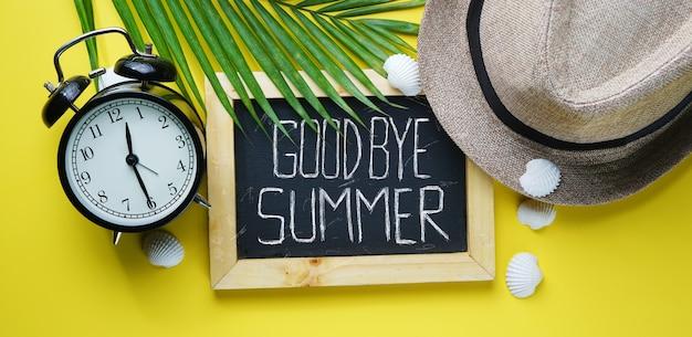 Alarm clock fedora hat, palm leaf, sea shells and blackboard room Premium Photo