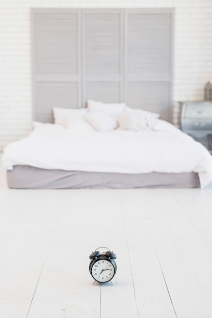 Alarm clock on floor near bed with white linen Free Photo