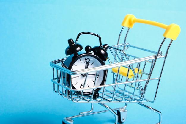 파란색 배경 복사 공간에 미니어처 쇼핑 트롤리에 알람 시계 프리미엄 사진
