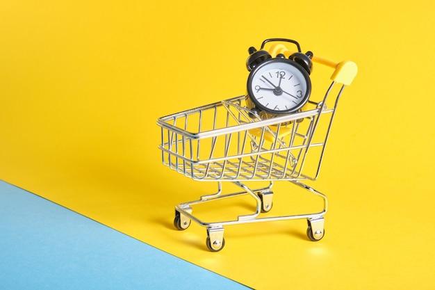 노란색 배경 복사 공간에 미니어처 쇼핑 트롤리에 알람 시계 프리미엄 사진