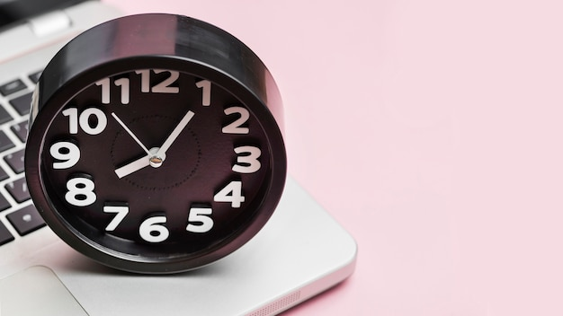 Alarm clock on laptop against pink background Free Photo