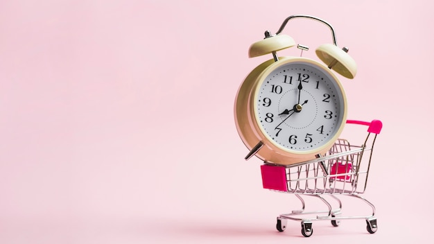 Alarm clock in miniature shopping trolley against pink background Free Photo