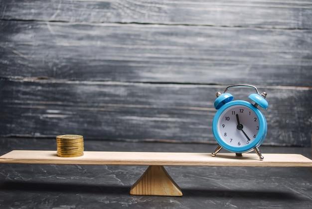 Alarm clock and money on the scales. Premium Photo
