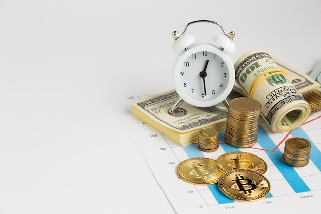 Alarm clock above money stack Free Photo