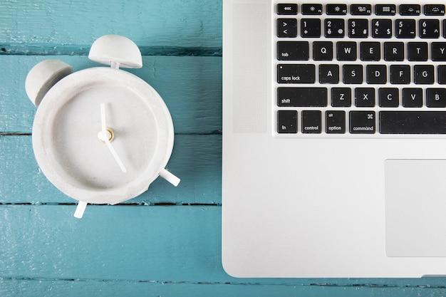 Alarm clock near laptop Free Photo