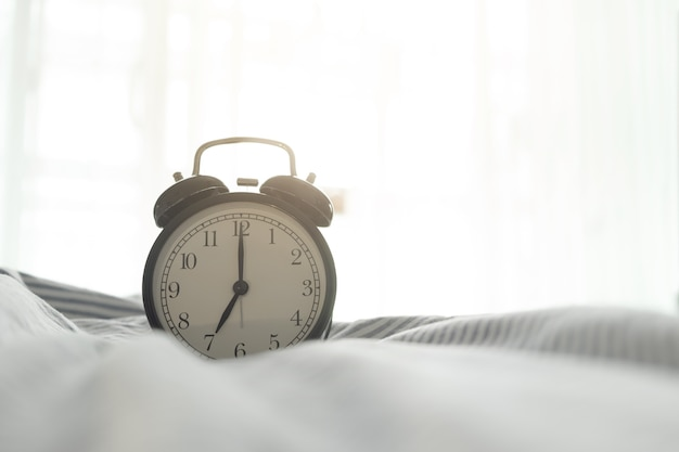 Alarm Clock On Bed In Bedroom With Morning Sun Light. Premium Photo