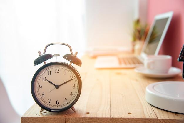 コーヒーカップとラップトップの作業テーブルの期限時間ビジネスの目覚まし時計 Premium写真