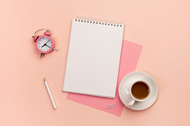 Будильник, карандаш, спиральный блокнот, бумага и чашка кофе на персиковом фоне Premium Фотографии