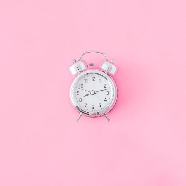 Alarm clock on pink background Premium Photo