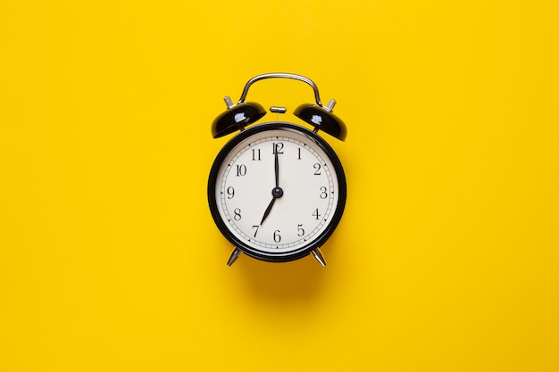 Alarm clock shows hour on a yellow background Premium Photo