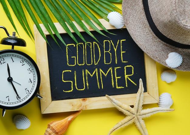 Alarm clock, starfish, fedora hat, palm leaf, sea shells and blackboa Premium Photo