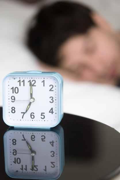 Alarm clock on table in front of sleeping man, vertical Free Photo