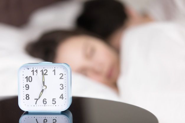 Alarm clock on table in front of sleeping young couple Free Photo