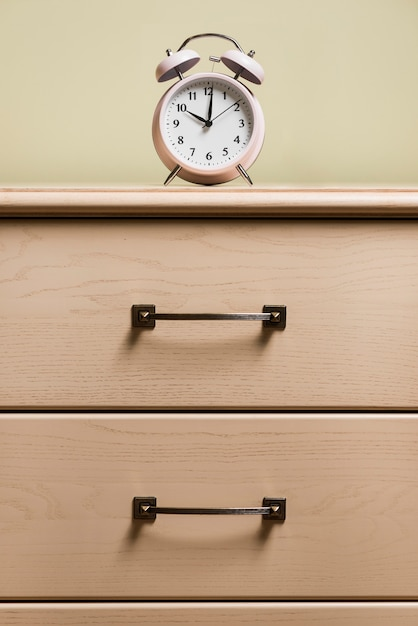 An alarm clock on top of wooden cabinet Free Photo