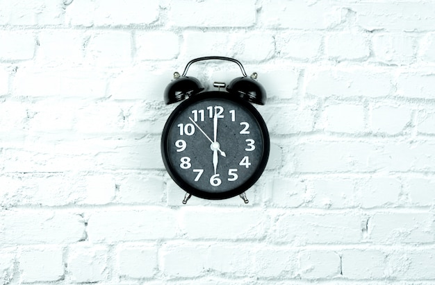 Alarm clock on white bricks Premium Photo
