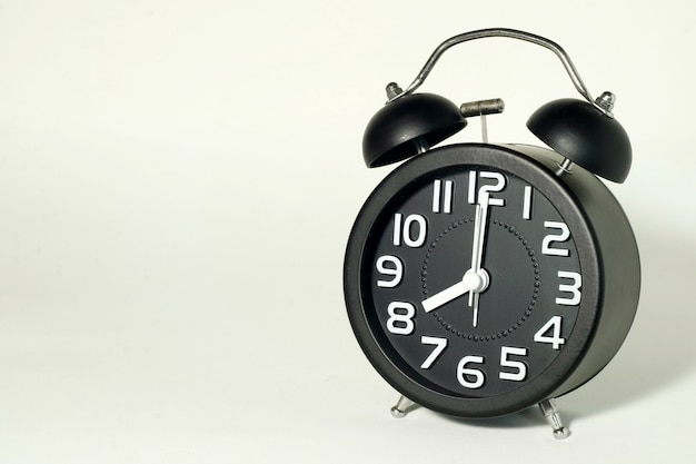 Alarm clock on white , showing time at 8 o'clock, it's late now. Premium Photo