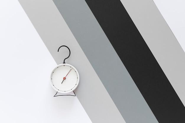 물음표 모양의 후크와 알람 시계. 배경 회색, 흰색, 검은 색 줄무늬. 평면도. 공간을 복사하십시오. 프리미엄 사진