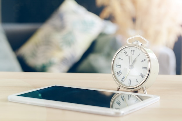 Alarm clock with cell phone on a wooden table Premium Photo
