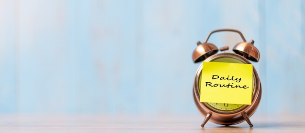 Alarm clock with daily routine note paper on wooden table Premium Photo