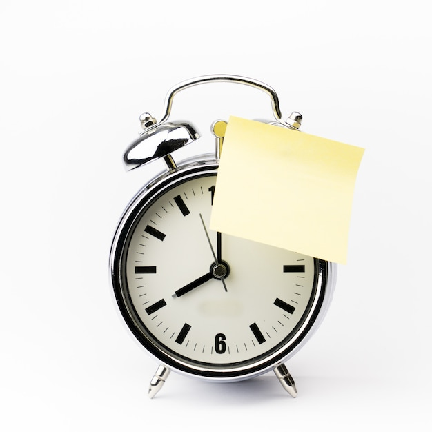 Alarm clock with sticky paper note on white background Premium Photo
