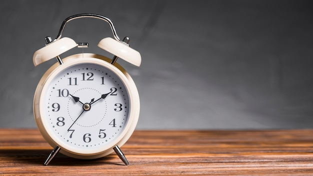 Alarm clock on wooden desk against gray background Free Photo