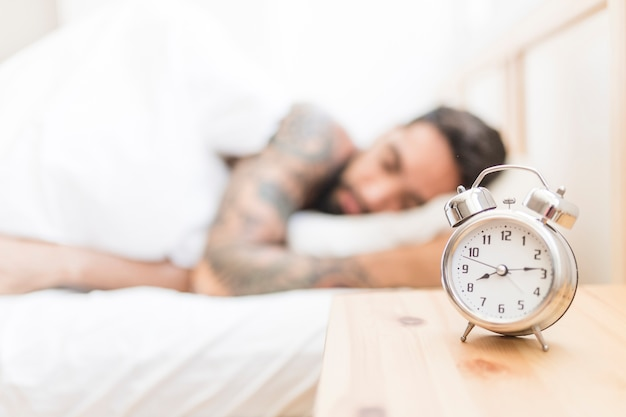 Alarm clock on wooden desk with man sleeping in background Free Photo