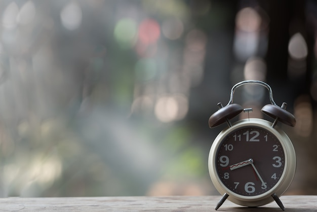Alarm clock on wooden table with green nature bokeh background. Premium Photo