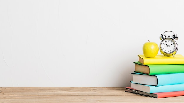 Alarm clock and yellow apple on stack of books Free Photo