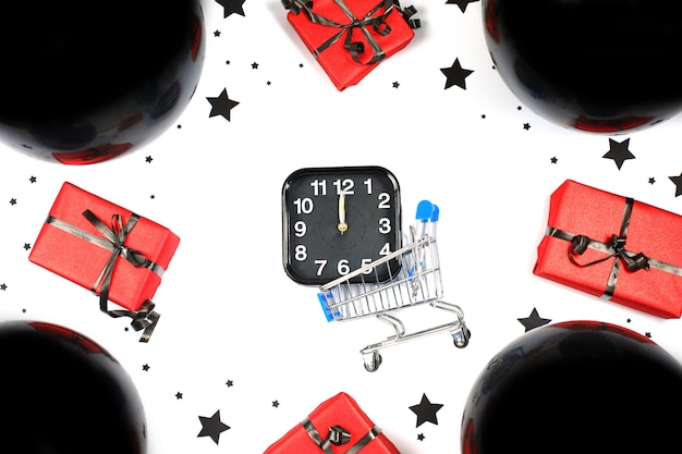Alarm and mini shopping cart with black baloons and gift boxes. shopping and sales composition. black friday sale. cyber monday. Premium Photo