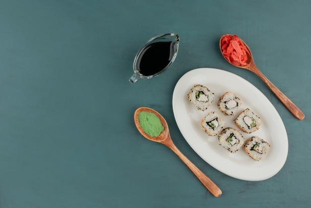 와사비, 절인 생강, 간장과 함께 하얀 접시에 알래스카 스시 롤. 무료 사진