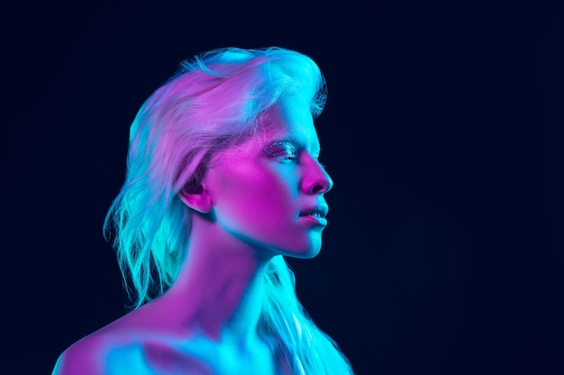 Albino girl with white skin, natural lips and white hair in neon light isolated on black studio background. Free Photo