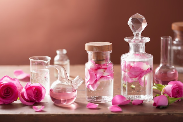 Алхимия и ароматерапия с розовыми цветами и колбами Premium Фотографии