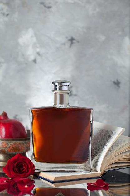 La bottiglia dell'alcool su un libro con i melograni e è aumentato Foto Gratuite