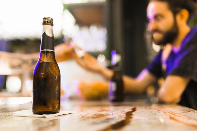 Alcohol bottle on tissue paper over the wooden table Free Photo