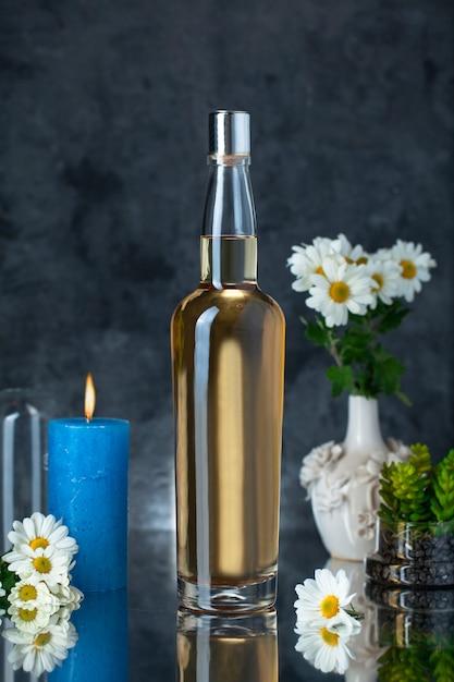 Бутылка алкоголя с цветами и свечой Бесплатные Фотографии