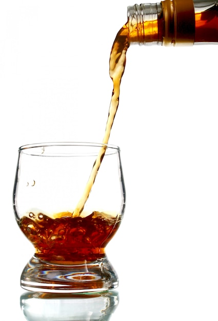 Alcohol drink pouring into glass Premium Photo