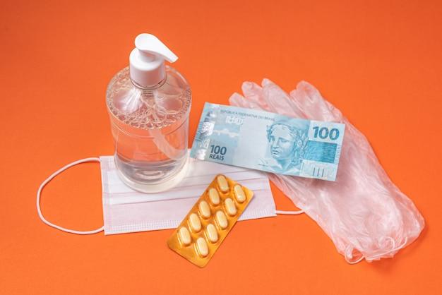 オレンジ色の壁にアルコールジェルコンテナー、サージカルマスク、薬、ブラジルのリアルマネー 無料写真