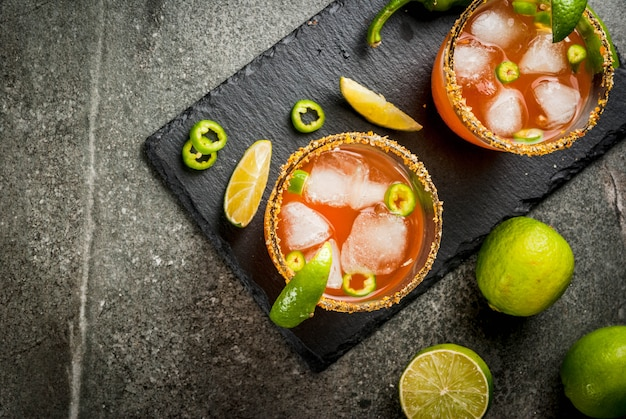 Alcohol. traditional mexican south american cocktail. spicy michelada with hot jalapeno peppers and lime. on a dark stone table. copyspace top view Premium Photo