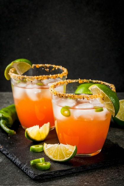 Alcohol. traditional mexican south american cocktail. spicy michelada with hot jalapeno peppers and lime. on a dark stone table. copyspace Premium Photo