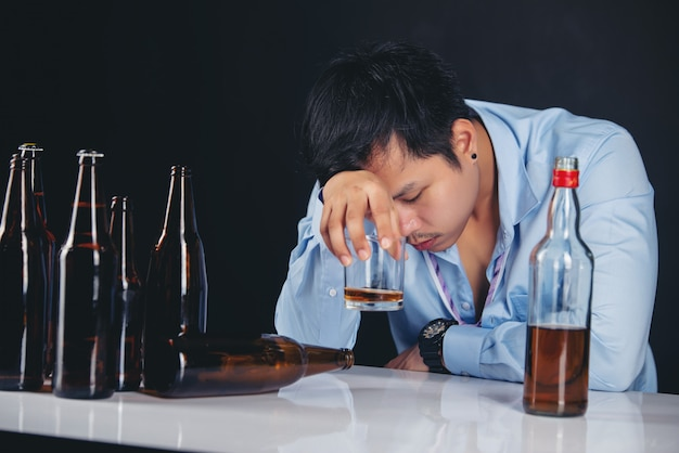 Alcoholic asian man drinking whisky with a lot of bottles Free Photo