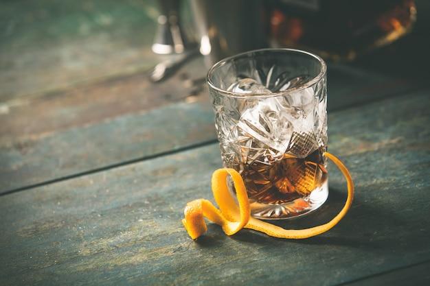 Alcoholic cocktail  with orange peel and ice Premium Photo