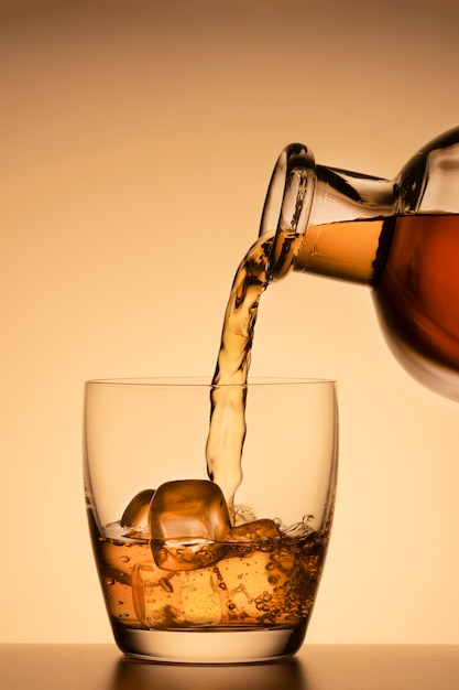 Алкогольный напиток, разлитый из стакана из бутылки на оранжевом золотом фоне. виски, коньяк или бурбонский виски. Premium Фотографии