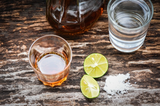 Alcoholic drinks and lemon salt on rustic wood background brandy in a glass with alcohol bottles and water, vodka rum cognac tequila and whiskey Premium Photo