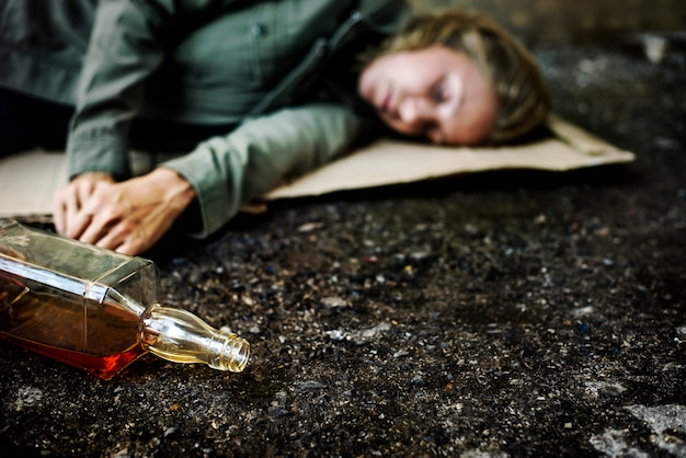 Alcoholic on the ground Premium Photo