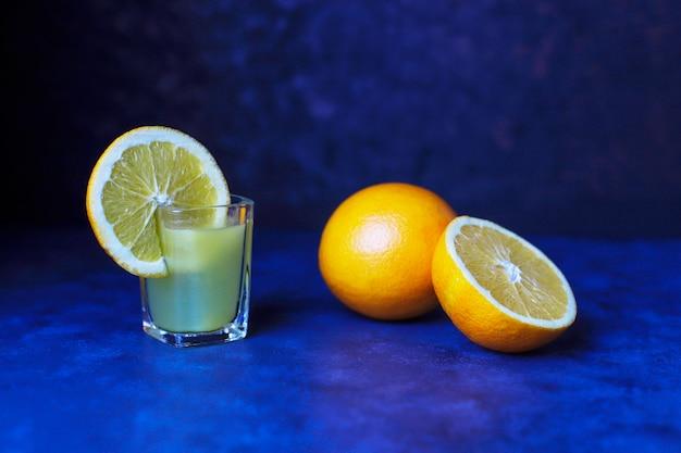 Alcoholic orange drink in shot glass with orange slice and orange on dark background Free Photo