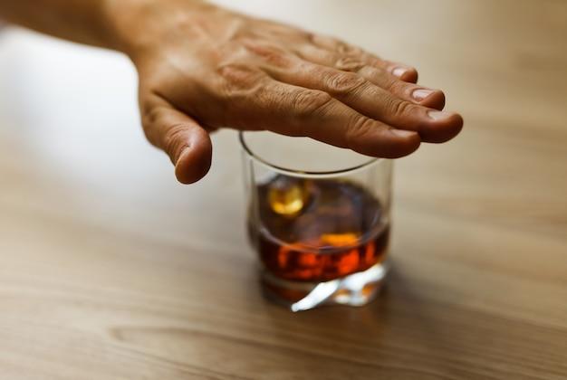Концепция алкоголизма. руки запирают цепь стаканом виски Premium Фотографии