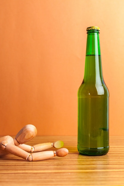 Alcoholism concept. wooden doll with alcohol drink Premium Photo