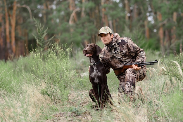 Alert hunter and dog in forest animal chasing. Premium Photo